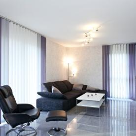 Wohnzimmer mit Sessel, Fußbank und Couch